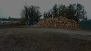 massive pile of chopped firewood in a dirt field