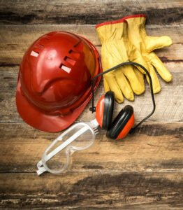 Red hard hat, yellow work gloves, orange ear protection, and protective eye goggles